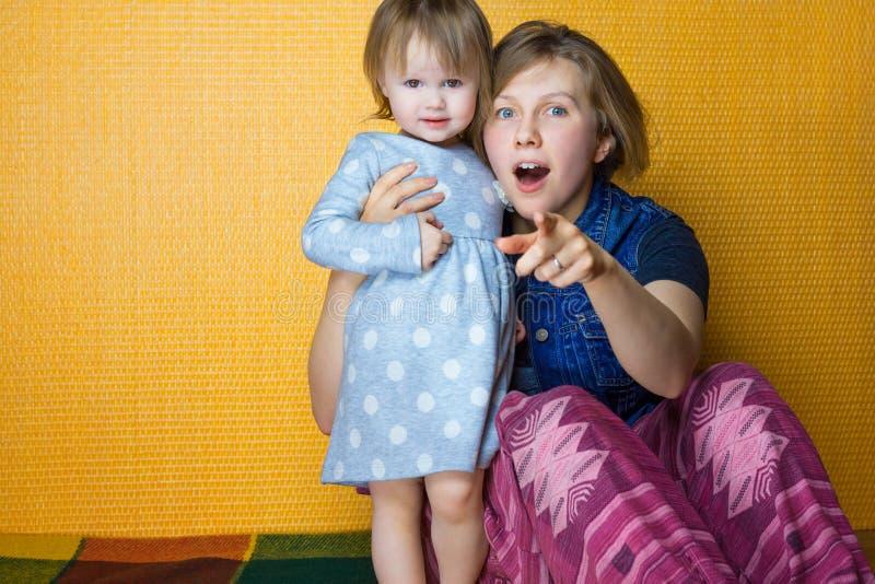 Retrato da mãe que abraça a filha da criança consideravelmente, olhar surpreendido da menina à câmera mulher, ponto da pessoa na  imagem de stock