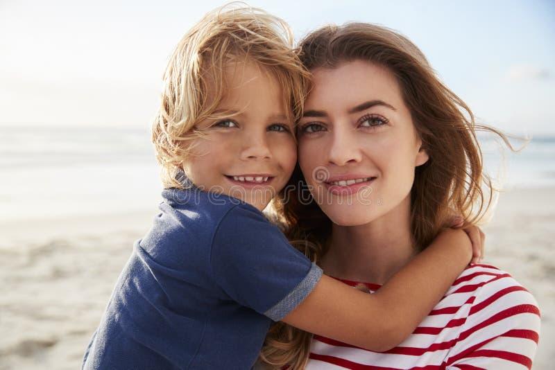 Retrato da mãe que abraça o filho em férias da praia do verão fotografia de stock