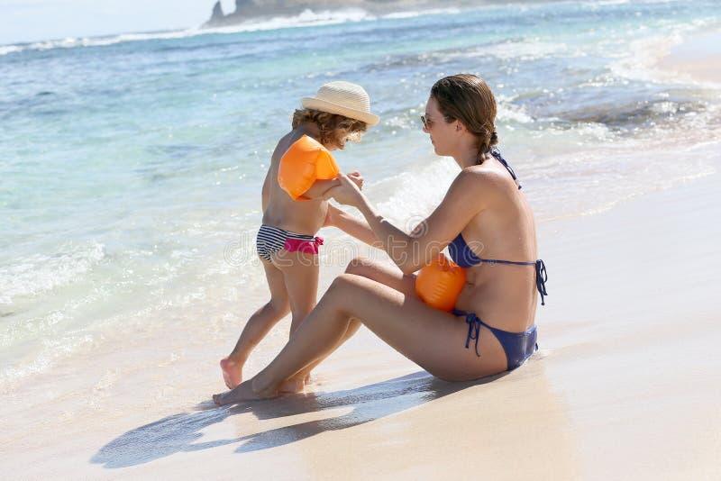 Retrato da mãe que ensina sua filha nadar na praia fotos de stock royalty free