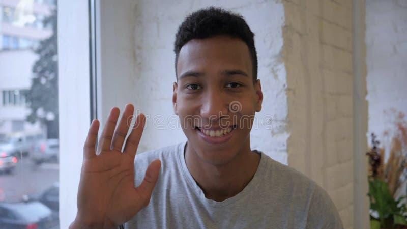 Retrato da mão de ondulação do homem afro-americano no interior do sótão foto de stock royalty free