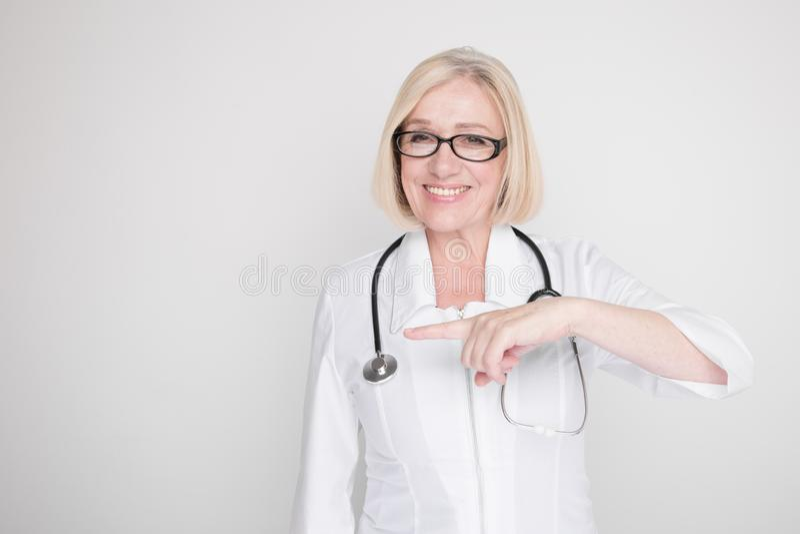Retrato da médica feminina apontando algo isolado no estúdio branco fotos de stock