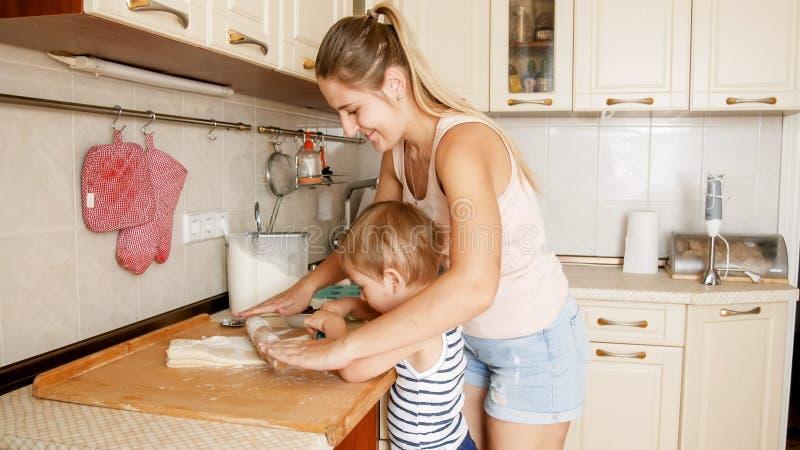Retrato da m?e com 3 da crian?a anos de cookies de cozimento do filho na cozinha na manh? Cozimento da fam?lia e cozimento em cas fotos de stock royalty free