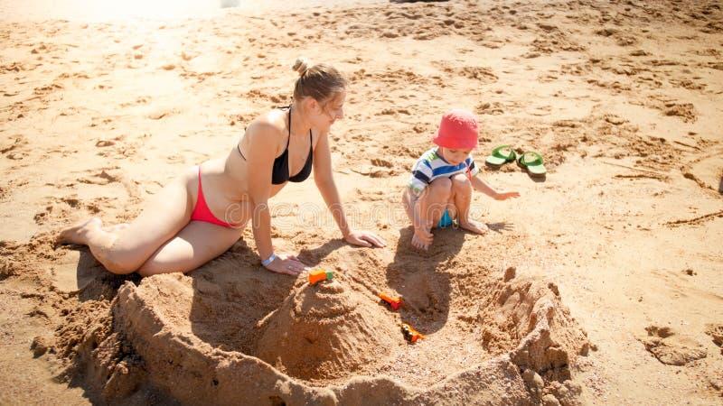 Retrato da m?e nova que ensina seus 3 anos dos castelos de constru??o do filho idoso da crian?a da areia na praia do mar Fam?lia imagens de stock