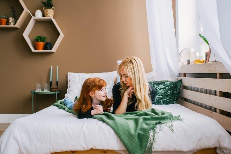 Retrato da mamã agradável e da filha pequena do ruivo em casa imagem de stock royalty free