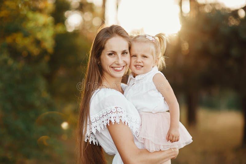 Retrato da matriz e da filha A mãe guarda uma menina em seus braços no fundo de um prado fotografia de stock
