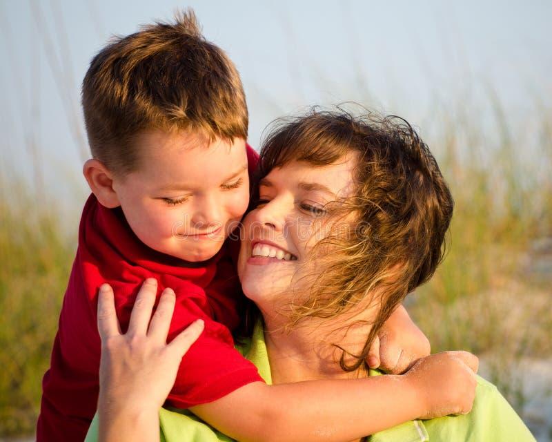 Retrato da matriz feliz e do filho que abraçam na praia foto de stock royalty free