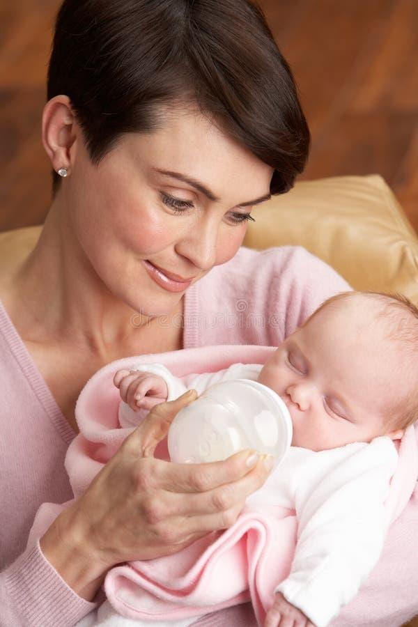 Retrato da matriz que alimenta o bebê recém-nascido em casa fotografia de stock