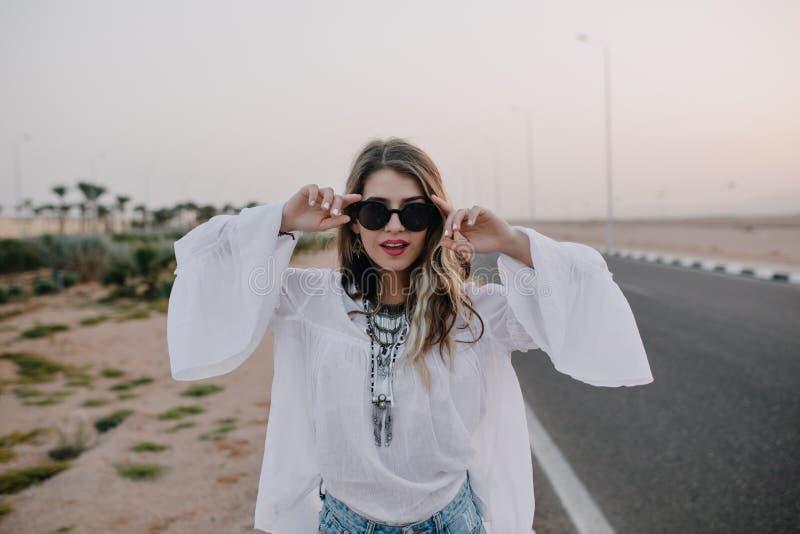 Retrato da menina ? moda graciosa em ?culos de sol pretos e na blusa branca que t?m o divertimento ao lado da estrada no ver?o ch foto de stock