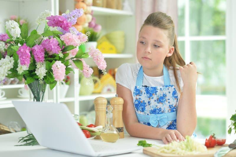 Retrato da menina adolescente bonito que usa o port?til ao preparar a salada fresca na mesa de cozinha fotografia de stock