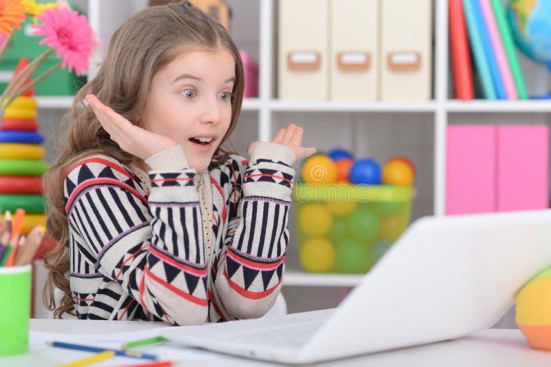 Retrato da menina adolescente emocional que usa o portátil em sua sala fotografia de stock