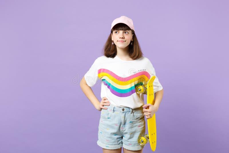 Retrato da menina adolescente pensativa na roupa v?vida que olha de lado, mantendo o skate amarelo isolado na cor pastel violeta fotos de stock