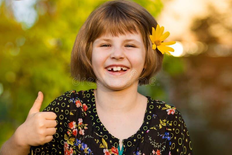Retrato da menina ador?vel com a flor nos cabelos, mostrando os polegares acima fotos de stock royalty free