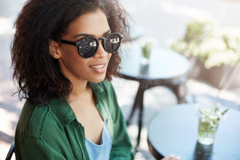 Retrato da menina africana bonita nova no relaxamento de descanso de sorriso dos sungasses no café no terraço fotografia de stock