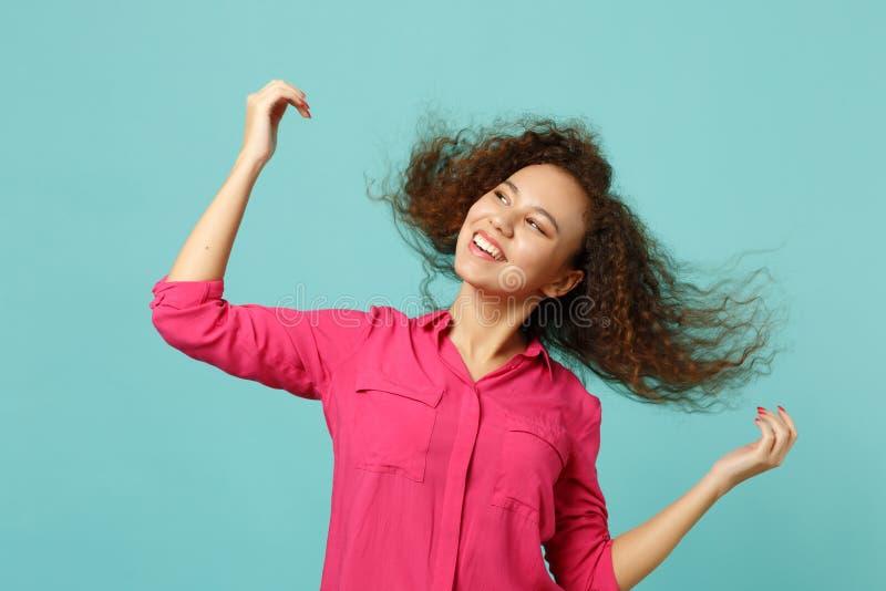 Retrato da menina africana de sorriso na roupa ocasional que salta com o cabelo de vibração isolado na parede azul de turquesa fotos de stock royalty free