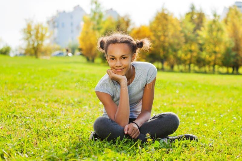 Retrato da menina africana que senta-se na grama verde fotografia de stock royalty free