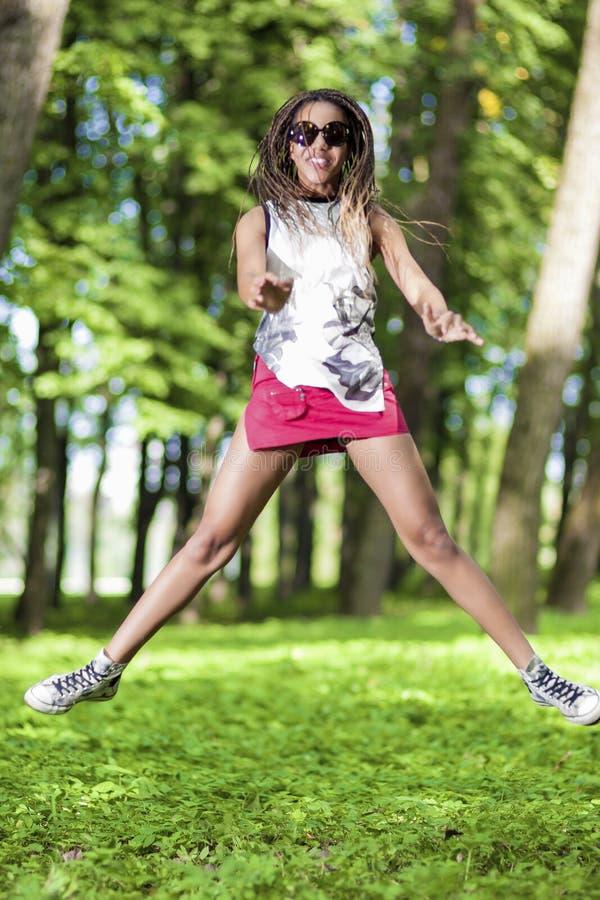 Retrato da menina afro-americano feliz e ativa do adolescente que faz um salto alto imagens de stock royalty free