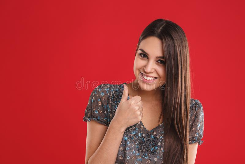 Retrato da menina alegre bonito bonita nova que sorri olhando a câmera sobre o fundo vermelho imagens de stock royalty free