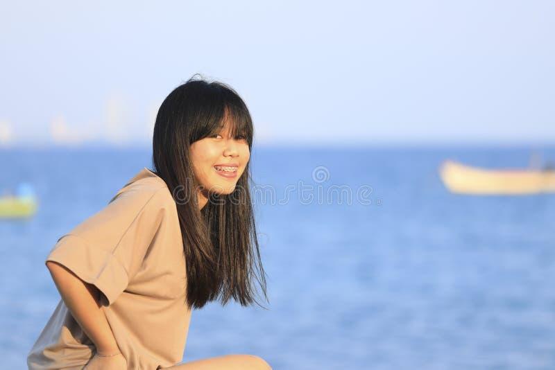 Retrato da menina asiática adolescente que senta-se na pedra perto do mar fotografia de stock