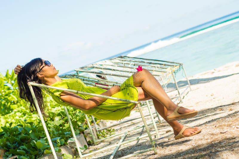 Retrato da menina asiática bonita nova que relaxa na rede na praia tropical imagem de stock