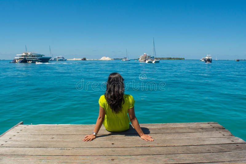 Retrato da menina asiática bonita nova que senta-se no cais que enfrenta o oceano fotografia de stock royalty free
