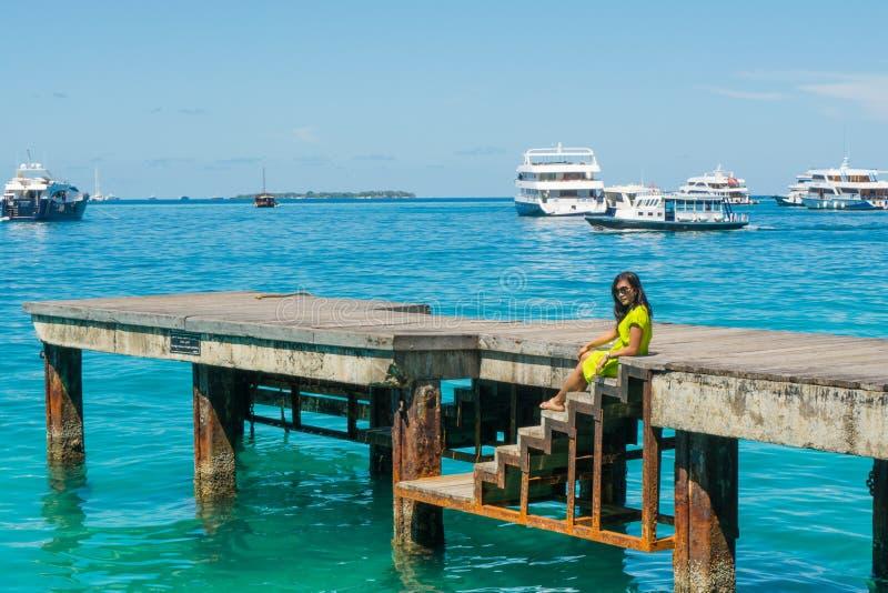 Retrato da menina asiática bonita nova que senta-se no cais que olha o lado do oceano imagem de stock