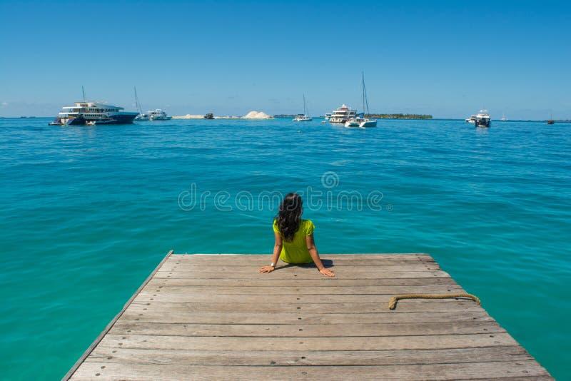 Retrato da menina asiática bonita nova que senta-se no cais que olha o oceano imagens de stock royalty free