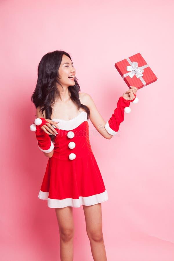 Retrato da menina asiática bonito de Santa Claus do Natal com presente vermelho fotografia de stock