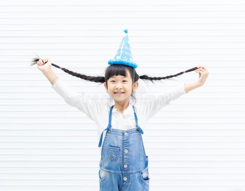 Retrato da menina asiática bonito pequena engraçada que sorri e que guarda os cabelos T-shirt vestindo e calças de ganga do pr imagens de stock