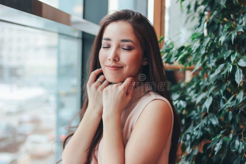 Retrato da menina asiática de sorriso da morena romântica encantador bonita perto da janela no café fotografia de stock