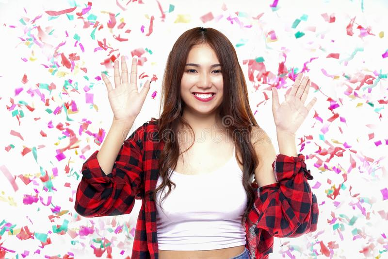Retrato da menina asiática do divertimento feliz com confetes coloridos no partido imagem de stock