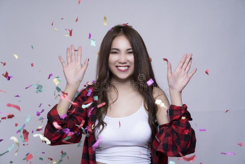 Retrato da menina asiática do divertimento feliz com confetes coloridos no partido imagem de stock royalty free