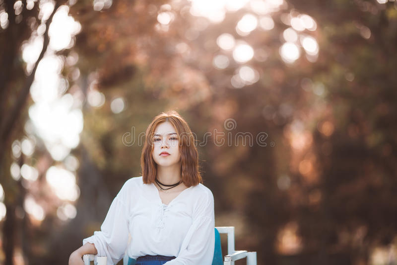 Retrato da menina asiática do moderno novo que levanta no fundo do bokeh da floresta do parque do autume fotos de stock