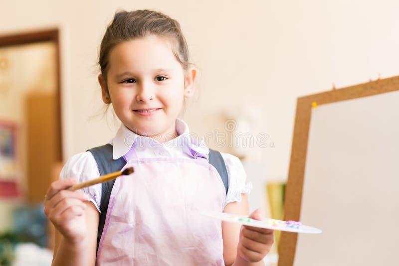 Retrato da menina asiática na pintura do avental imagem de stock royalty free
