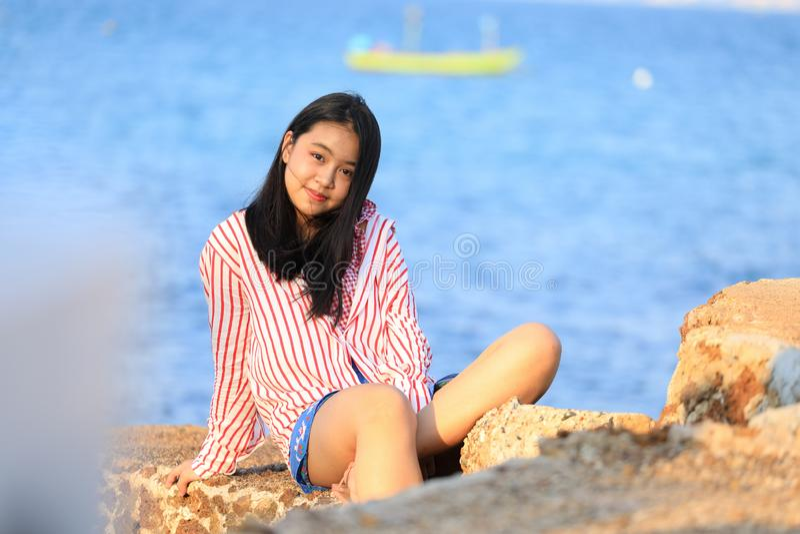 Retrato da menina asiática nova que senta-se na pedra perto do mar foto de stock royalty free