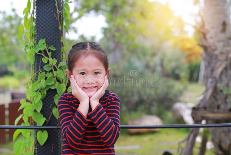 Retrato da menina asiática pequena de sorriso da criança com toque de seu mordente que olha em linha reta na câmera no jardim da  fotografia de stock royalty free