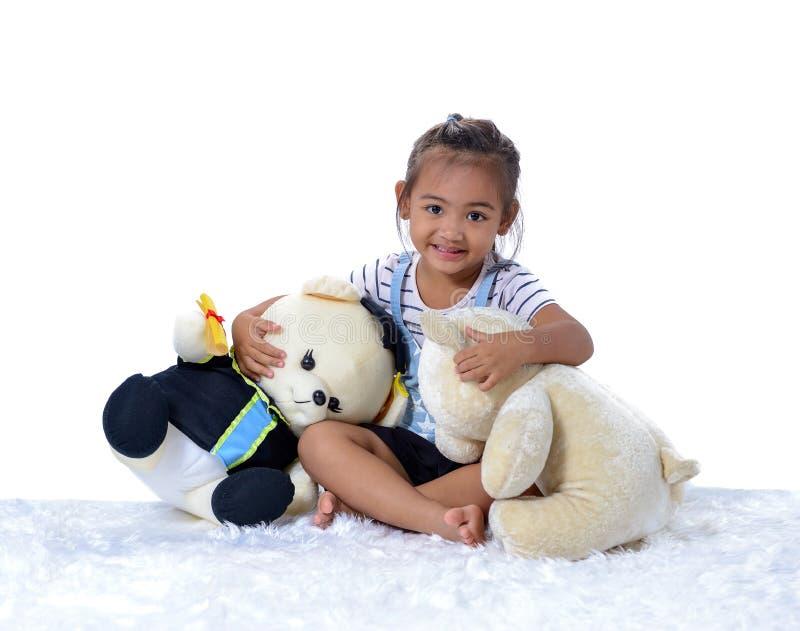 Retrato da menina asiática pequena feliz com as duas bonecas isoladas no fundo branco imagem de stock royalty free