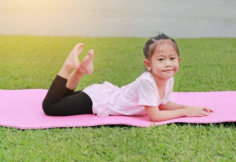 Retrato da menina asi?tica pequena da crian?a que faz a ioga no parque p?blico foto de stock royalty free