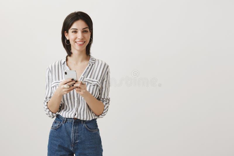 Retrato da menina atrativa que recebeu o cumprimento sobre o smartphone novo Mulher urbana à moda bem sucedida que guarda o telef imagens de stock