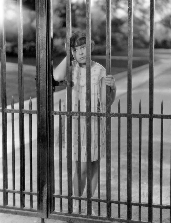 Retrato da menina através das barras da cerca (todas as pessoas descritas não são umas vivas mais longo e nenhuma propriedade exi fotografia de stock