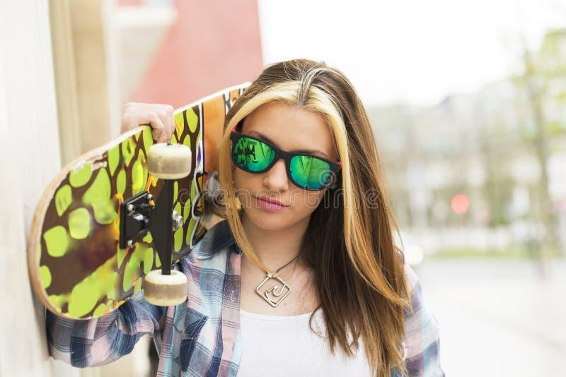 Retrato da menina bonita com óculos de sol e skate, urbano fotos de stock royalty free