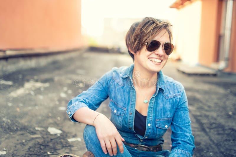 Retrato da menina bonita com óculos de sol que ri e que sorri ao falar com amigos, pendurando para fora no telhado da construção  imagens de stock royalty free