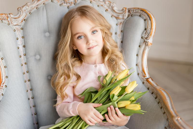 Retrato da menina bonita bonita com as tulipas amarelas das flores que sentam-se na poltrona, sorrindo Foto interna Tema da mola fotos de stock royalty free