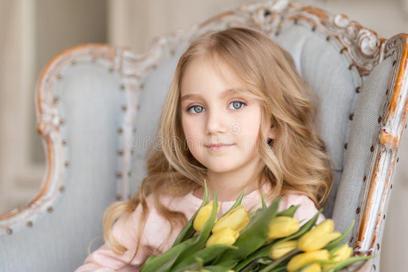 Retrato da menina bonita bonita com as tulipas amarelas das flores que sentam-se na poltrona, sorrindo Foto interna Tema da mola  imagem de stock