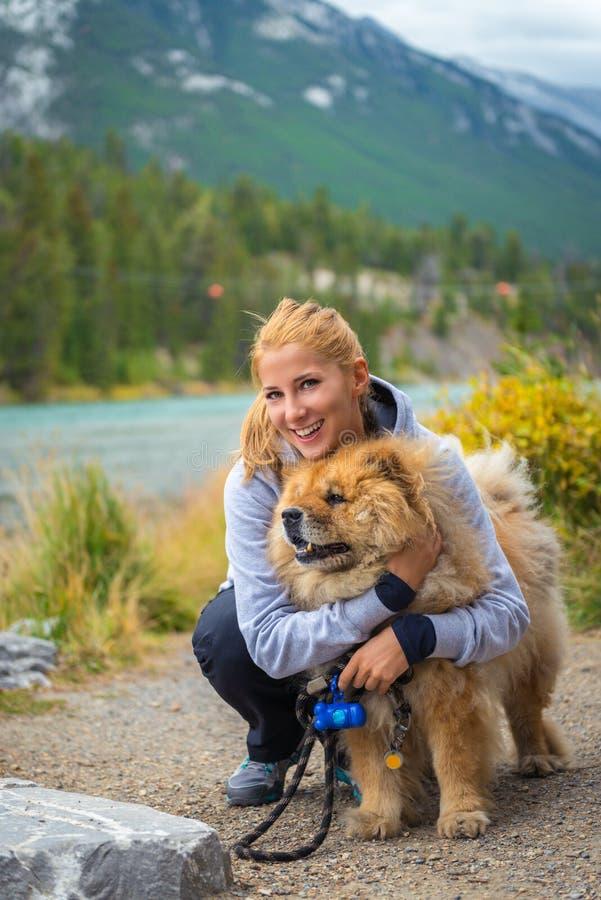 Retrato da menina bonita com cão da comida-comida fotografia de stock