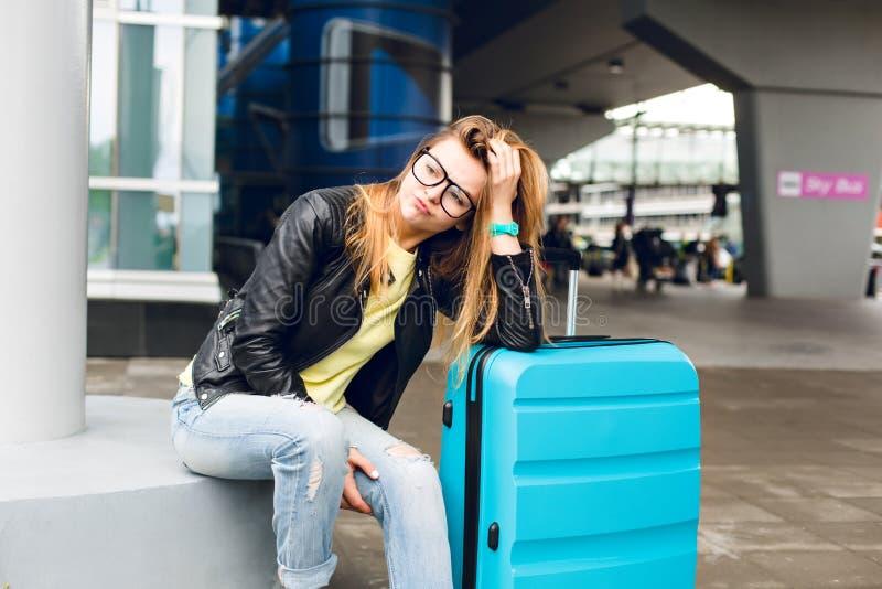 Retrato da menina bonita com cabelo longo nos vidros que sentam-se fora no aeroporto Veste a camiseta amarela com revestimento pr imagem de stock royalty free