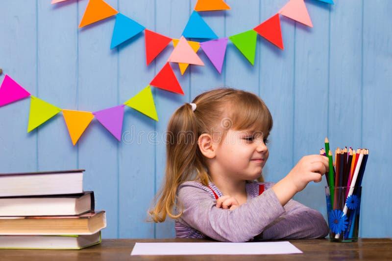 Retrato da menina bonita na sala de aula Estudante pequena que senta-se em uma mesa e em um estudo foto de stock