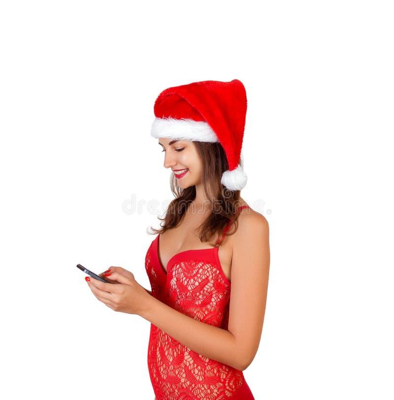 Retrato da menina bonita no roupa de banho e no chapéu do Natal com telefone celular à disposição a mulher emocional no chapéu ve fotografia de stock royalty free