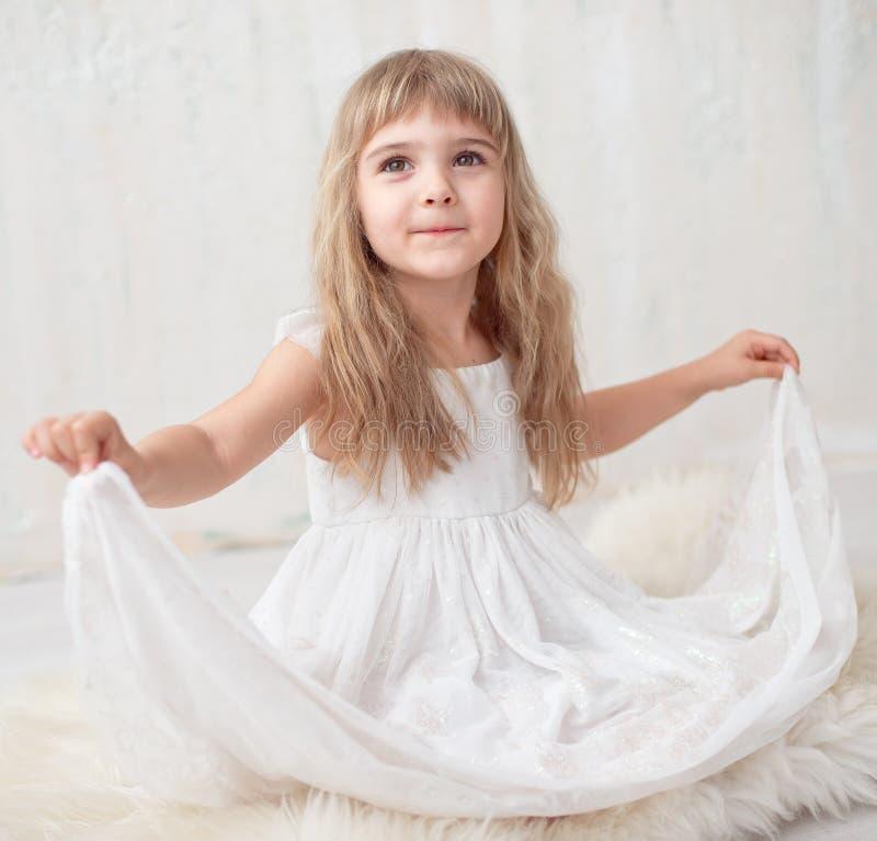 Retrato da menina bonita no vestido branco, olhando a câmera e o sorriso, estando contra o fundo cinzento fotografia de stock royalty free