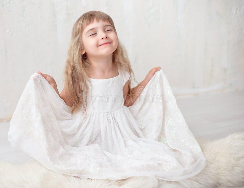 Retrato da menina bonita no vestido branco, olhando a câmera e o sorriso, estando contra o fundo cinzento imagens de stock