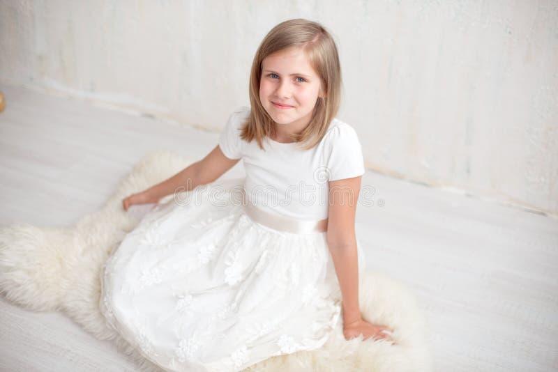 Retrato da menina bonita no vestido branco, olhando a câmera e o sorriso, estando contra o fundo cinzento imagem de stock